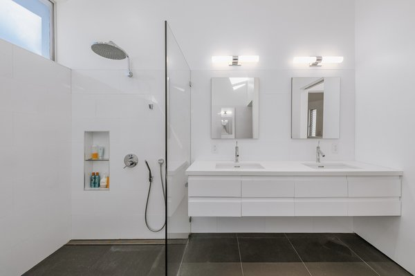 The master bath also features an open shower with a glass partition and a dual vanity.