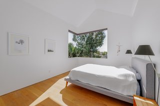 The master bedroom has a butt glass window and engineered white oak floors.