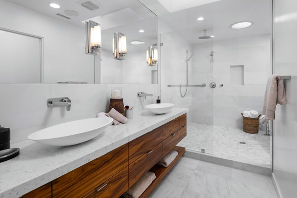 The renovation added a spacious master bathroom with high-end finishes, a dual vanity, and a large walk-in shower.
