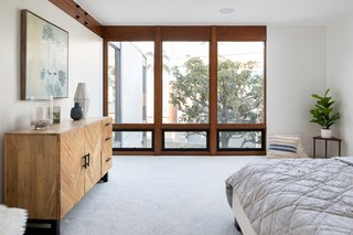 The master bedroom has a wall of windows trimmed with wood.