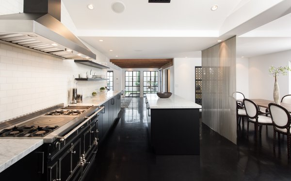 The kitchen features black cabinetry, a white subway tile backsplash, marble countertops, and a center island. There is also a screen that separates the kitchen from the dining area.