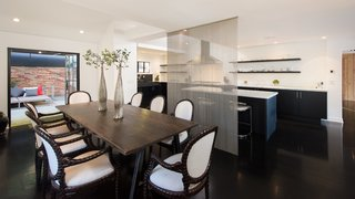 The dining area features steel-framed French doors which open to an outdoor terrace.