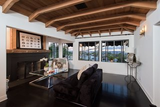 An additional sitting area has a wood-beamed ceiling and a wood-burning fireplace.