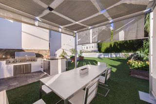 An outdoor, shaded barbecue space just off the garden is perfect for al fresco dining.