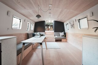The minimalist boat is fitted with bespoke wall sconces and custom-made upholstery.