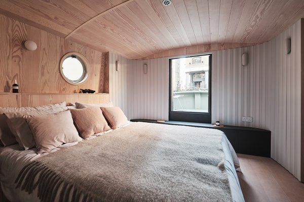 The houseboat has a single bedroom with a round porthole—lest you forget where you are staying.