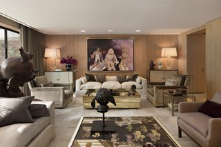 In the elegant, wood-paneled television room, a painting by Richard Prince hangs above a custom-made sofa by Jonas and a brass Gabriella Crespi table from Nilufar.