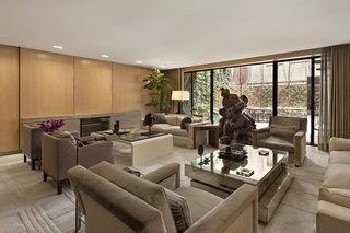 A Dopey sculpture by Paul McCarthy holds center stage in the television room. Floor-to-ceiling glass sliding doors lead to the outdoor space.