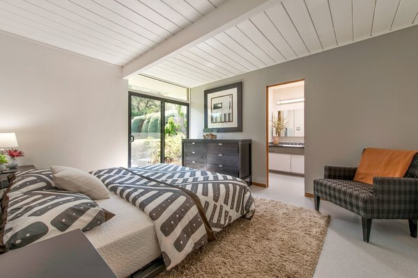 The master bedroom features an ensuite bathroom and a spacious walk-in closet. Sliding glass doors lead to a lovely little outdoor terrace.