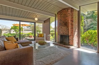 The living room is anchored by an original brick fireplace and surrounded by walls of glass.