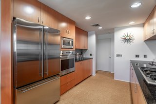 The updated kitchen has black galaxy granite counters, a gas cooktop, recently installed stainless steel appliances, and cork flooring.
