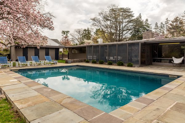 Neutra framed the outdoor area with a long pool house that closes off the space and provides some privacy. The pool house has changing rooms, a bathroom, and storage space for outdoor equipment. The swimming pool is set in a natural flagstone terrace.