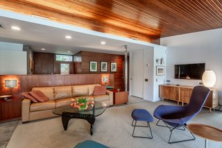 The entryway greets visitors with cedar-paneled ceilings and a strong midcentury vibe.