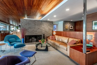 A massive stone wall with a double-sided fireplace divides the living space.