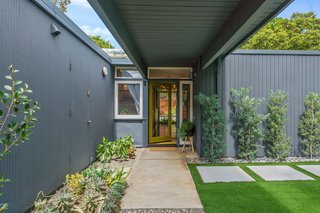 The fence in front of the house creates an L-shaped courtyard. The entrance is tucked behind the private gate.