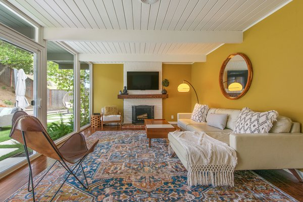 The living room has a wood-burning fireplace and a wall of windows with sliding glass doors leading to the backyard.