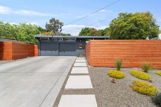 The home's exterior has a fresh coat of paint,  a new modern fence, and beautiful landscaping.