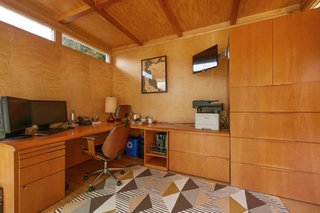 The studio is insulated, wired for electricity, and air conditioned. The wood-clad interior features a custom-built office system.