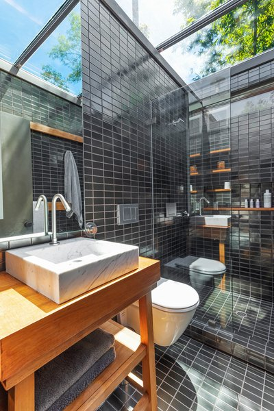 An elegant black-tiled bathroom with a skylight.