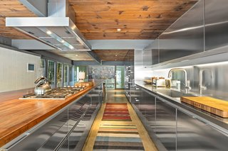 The kitchen is outfitted with Miele appliances. The faucet and stainless steel cabinets are by Boffi.
