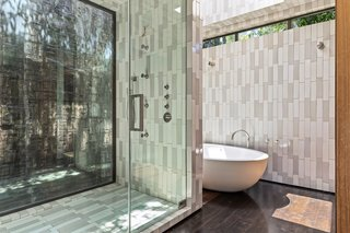 The deluxe bathroom has a deep soaking tub and vertically positioned subway tiles.