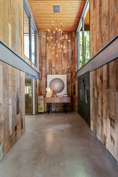 The Entry Pairs Rustic Reclaimed Oak Walls With A Poured Concrete Floor Natural Light