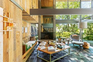 A dramatic mirror-paneled fireplace adds depth, and a wall of windows floods the space with sunlight.
