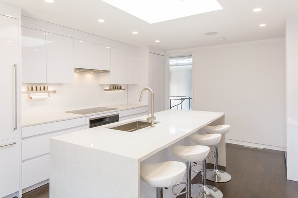 The bright, white eat-in kitchen features Leicht cabinetry, Miele appliances, and quartz countertops.