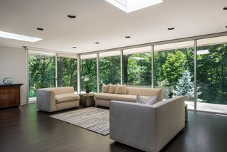 Floor-to-ceiling windows take in expansive forest views.