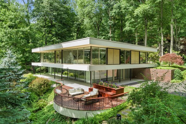 Designed by Arthur Witthoefft of Skidmore, Owings & Merrill in 1961, this five-bedroom, five-bathroom midcentury house is set in the woods of Armonk, New York. The 5,000-square-foot home features full-height walls of glass, a wraparound floating terrace, and a quiet deck that overlooks the site's sylvan surroundings.