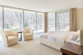 The master suite is located in a corner of the home and features floor-to-ceiling glass windows.