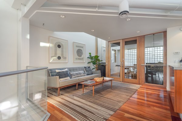 The kitchen overlooks an additional sitting area and a home office separated by glass doors.