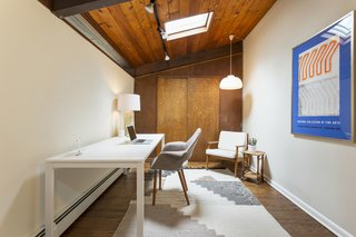 A cozy home office is brightened by a skylight.