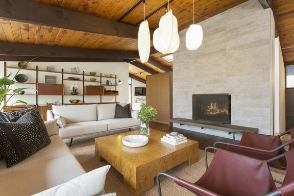The living room features a dramatic stone fireplace and vaulted tongue-and-groove ceilings.