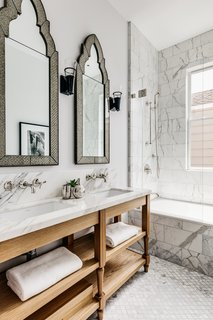 The guest bath features two sinks and lots of marble.