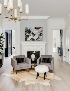 A marble fireplace anchors this sitting area. Two doors lead back to the open-plan living/dining/kitchen area.