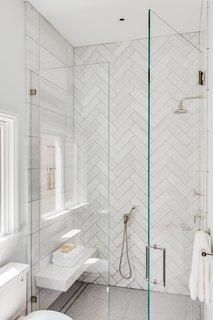 The stylish glass-enclosed shower features two contrasting types of tile.