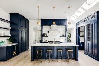 The main level features a bold blue kitchen illuminated by skylights.