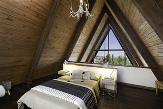 The lofted bedroom enjoys a view of the treetops.