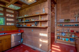 The kitchen has exposed concrete block walls and open shelving.