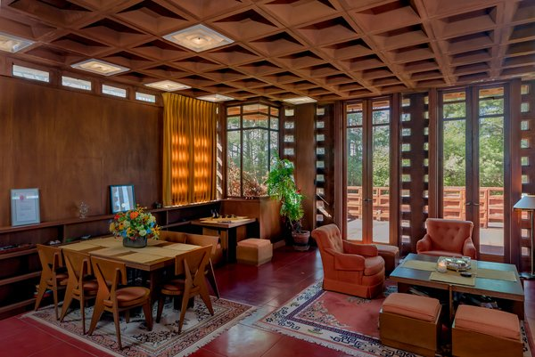 The living room features a red concrete floor and warm Philippine mahogany furniture designed by Wright.