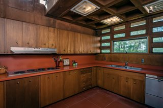 Philippine mahogany cabinetry in the kitchen echoes the rest of the home. The original red countertops pick up the red from the concrete floors.