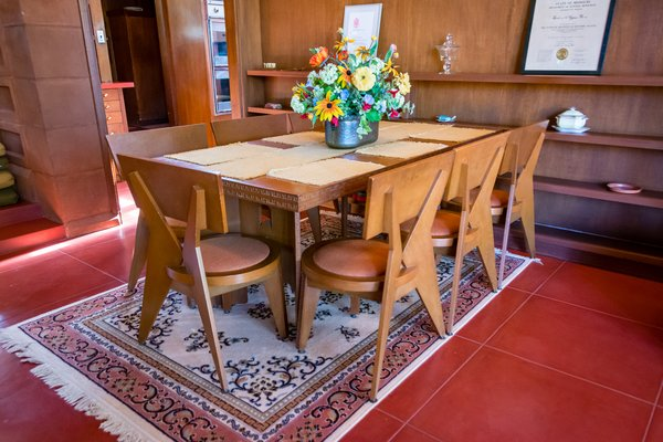 Wright crafted the dining table and chairs out of Philippine mahogany and and fabric-covered, foam cushions. All of the furniture designed by Wright in the home is also included in the sale.