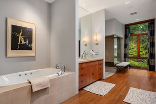 The master bath has a steam shower and a jetted tub. Floor-to-ceiling windows keep the interior bright.