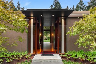 The grand entrance to the home features a full-height steel pivot door.