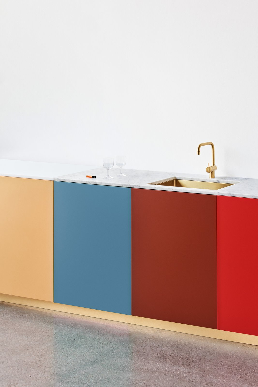 Kitchen, Undermount Sink, Concrete Floor, Marble Counter, and Colorful Cabinet The bright, bold panels are paired with classic features like marble countertops and playful on-trend elements like a brass faucet and sink.  Best Photos from Get a Designer Kitchen on an IKEA Budget With Reform's New Fronts and Tops