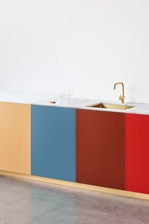 The bright, bold panels are paired with classic features like marble countertops and playful on-trend elements like a brass faucet and sink.