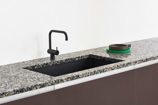 The black matte faucet, paired with a granite countertop, makes a bold, contemporary statement.
