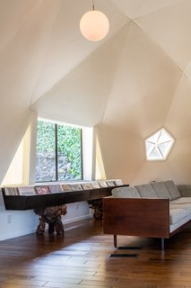 The geometric room is punctuated with windows and pentagon-shaped skylights.
