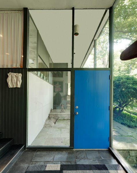 """The house is so Neutra, yet in a more wooded setting and perched high above the river,"" says the listing agent Rick Distel. The front door is painted a royal blue and framed by glass windows."